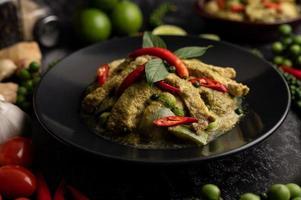 curry vert de porc en plaque noire avec des épices sur fond de ciment noir photo