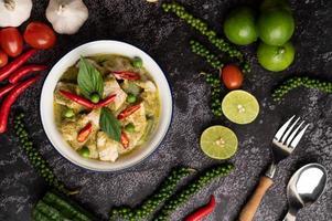 curry vert de porc dans un bol blanc avec des épices sur un ciment noir photo