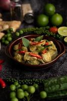curry vert de porc dans un bol marron avec des épices sur un ciment noir photo