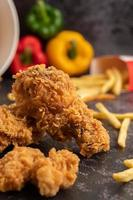 poulet frit et frites sur sol en ciment noir. photo