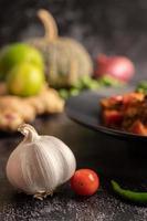 ail, tomates et piment sur fond de ciment noir photo