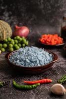 riz aux fleurs de pois papillon dans une tasse brune aux épices sur ciment noir. photo
