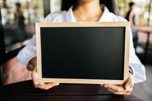 femme tenant un tableau noir au café photo