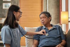 femme médecin vérifiant la santé d'un patient asiatique âgé de sexe masculin à la maison. photo