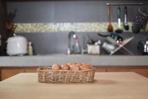 des œufs frais de la ferme entassés dans des paniers en bois dans la cuisine de la maison. photo