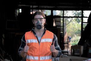 jeune charpentier pouce vers le haut et sourire à l'usine de bois. photo