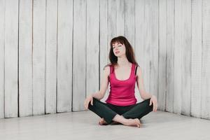 fille en haut rose, assise en tailleur sur le sol, souriante photo
