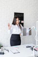 jeune femme latine en chemise blanche enseignant l'anglais en ligne photo