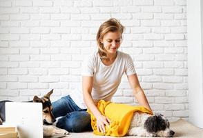 drôle de jeune femme en plaid jaune assis sur le sol avec ses chiens photo