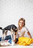 femme en plaid jaune assise sur le sol jouant avec ses chiens photo