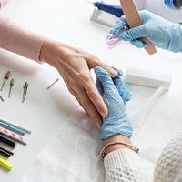 maître de manucure en gants à l'aide d'une lime à ongles pour polir l'ongle d'un client photo