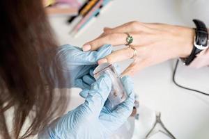 maître de manucure en masque et gants faisant tamponner au client photo