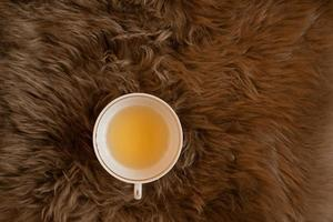 une tasse de thé vert sur le plaid en fourrure marron moelleux. photo