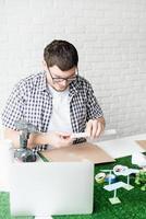 jeune homme enseignant en ligne faisant un mannequin d'énergie renouvelable photo