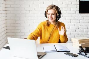 jeune femme dans des écouteurs noirs étudiant en ligne à l'aide d'un ordinateur portable photo
