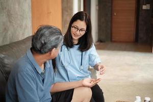 soins à domicile, femme médecin aidant un patient à prendre des médicaments photo