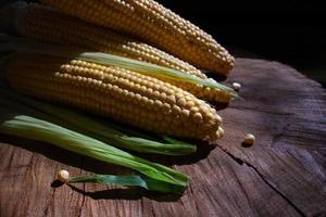 épis de maïs avec des feuilles sur fond en bois. nourriture de légumes frais photo