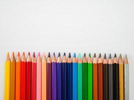 Ligne de crayons de couleur transparente sur fond de papier de peinture blanche photo