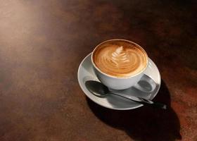 tasse d'art latte chaud dans la lumière de l'après-midi sur une table en bois photo