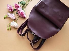 sac à dos en cuir pour femmes et fleurs sur fond marron clair photo