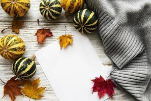 feuilles d'érable d'automne, citrouilles et écharpe en laine sur un fond en bois. photo