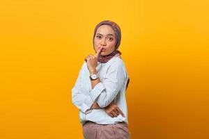 belle femme asiatique faisant un doigt sur les lèvres bouche silencieuse geste silencieux photo