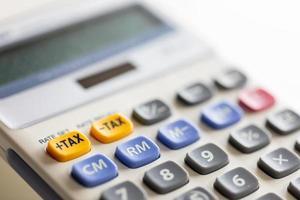mise au point sélective sur le bouton jaune de la calculatrice en plus des taxes. photo