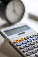 mise au point sélective sur le bouton plus taxe de la calculatrice avec horloge floue. photo