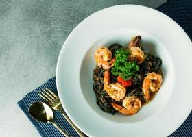 spaghettis à l'encre de seiche et crevettes épicées pour le déjeuner ou le dîner photo