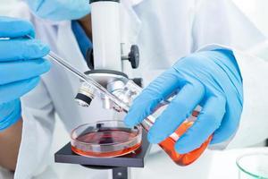 biochimiste scientifique asiatique avec un microscope en laboratoire. photo