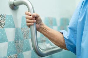 Asian senior woman patient utiliser la sécurité de la poignée dans les toilettes photo