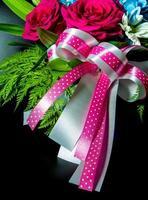noeud de ruban, point argenté et rose au beau bouquet de fleurs photo