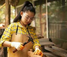 Femme debout builder worker hammering nail dans la planche de bois photo