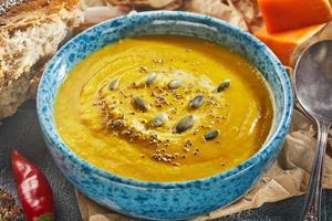 soupe à la crème de couleur orange à base de potiron, oignon, poivre photo