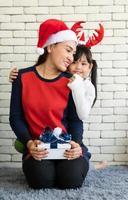 une mère asiatique donne un cadeau de noël à sa fille photo