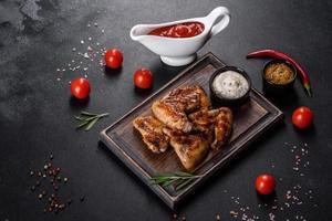 ailes de poulet épicées grillées sur fond sombre avec épices et herbes photo