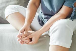 femme assise sur le canapé et tient son pied souffrant de douleurs aux pieds photo