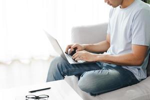 jeune homme assis sur le canapé en train de taper sur l'ordinateur portable pour travailler en ligne. photo