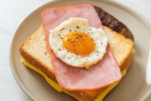 pain grillé garni de fromage jambon et œuf au plat avec saucisse de porc photo