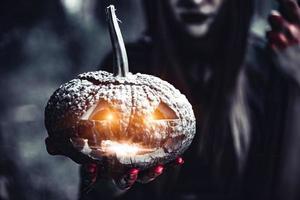lanterne citrouille dans la main de la sorcière. vieille femme dans la forêt sombre photo