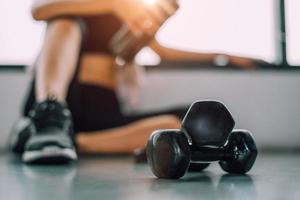 gros plan d'haltères avec exercice femme entraînement en salle de fitness photo