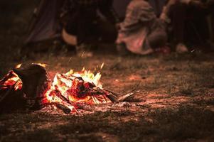 allumer un feu de joie avec des touristes assis autour d'un feu de joie lumineux photo