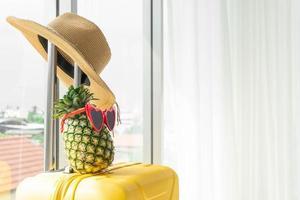 chapeau et ananas sur valise à l'hôtel avec espace de copie photo