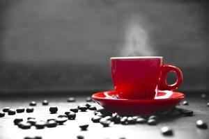 tasse de café rouge avec de la fumée et des grains de café photo