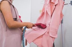 Femme utilisant un fer à repasser pour repasser une chemise de mode photo