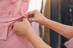 Gros plan sur une fille de créateur de mode féminine faisant l'ajustement à la main photo