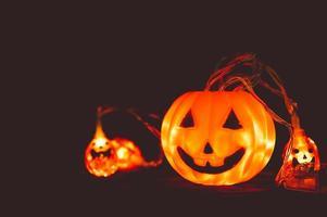 citrouille d'halloween et lumière dans l'obscurité photo