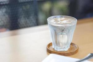 eau minérale en verre sur table en bois avec fond abstrait photo