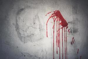 goutte de sang rouge sur le mur d'une maison abandonnée photo