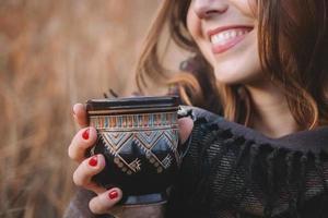 belle femme sourit et tient une tasse avec un verre photo